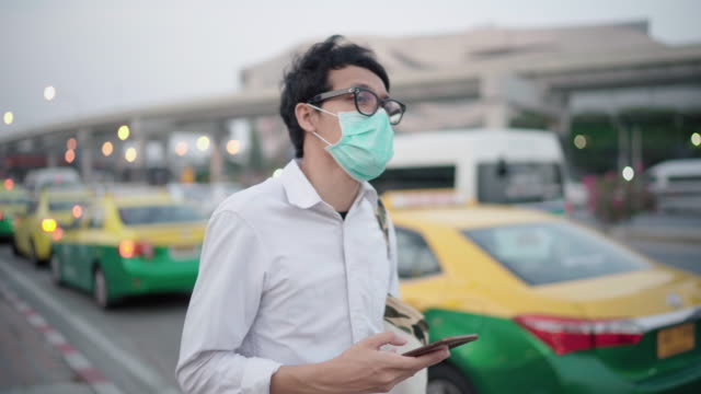 freiberufler trägt eine gesichtsmaske und überprüft uber / steuer - smartphone mit corona app stock-videos und b-roll-filmmaterial