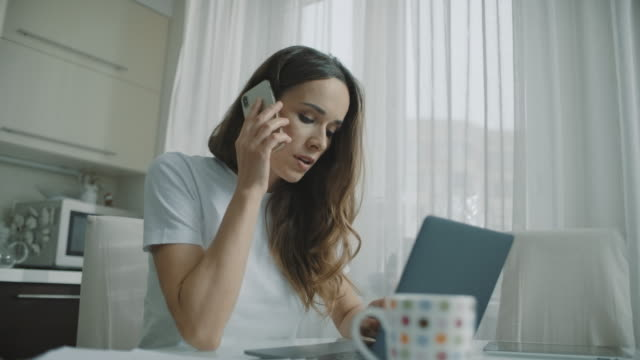 Freelancer woman talking phone at home kitchen. Female person using mobile phone