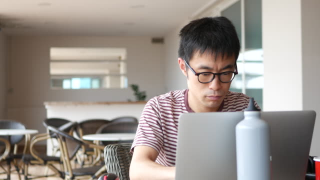 Freelancer working remotely A mid adult man sitting at an open space work lounge, working on his computer. handsome people stock videos & royalty-free footage
