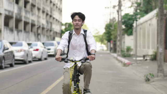 Freelancer young man driving his bicycle on the street in city