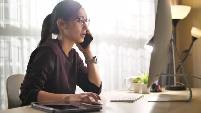 vidéos et rushes de freelancers working remotely support tout en parlant au téléphone à la maison - travaux maison