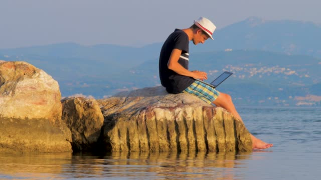 Freelancing guy working near the rocks and the sea. Business man on vacation in a tropical desert paradise. Preparing to pitch high in the mountains, on seaside. 4G, 5G connection background