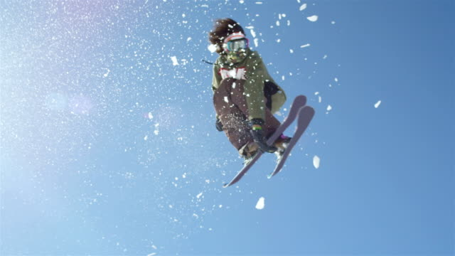 SLOW MOTION CLOSEUP: Freestyle skier jumping big kicker and flying over the sun in snowy mountains video