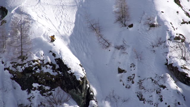 Freestyle skier jumps off a cliff into an avalanche