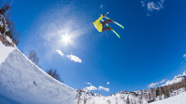 Freestyle skier performing jump stunt in a snow park video