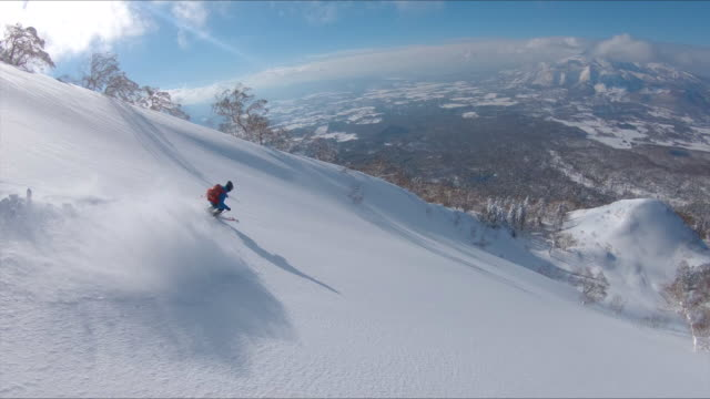 drone: freestyle skier shredding the snow while riding in the scenic mountains. - sci video stock e b–roll