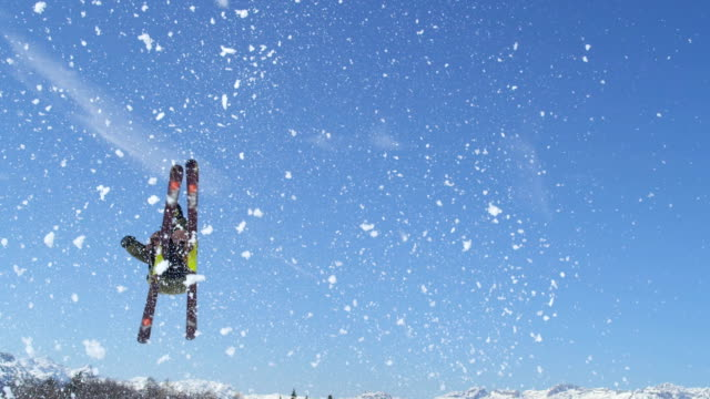 SLOW MOTION CLOSE UP: Freestyle skier skiing over the kicker and jumping big in sunny snowpark video