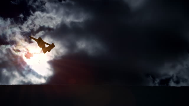 SLO MO Freestyle snowboarder jumping in the half-pipe with clouds in the background