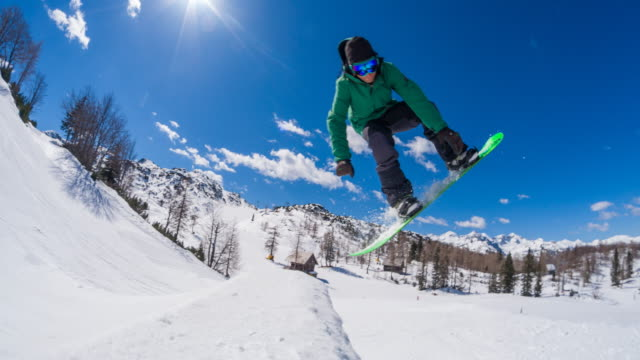 Freestyle snowboarder performing jump stunt in a snow park video