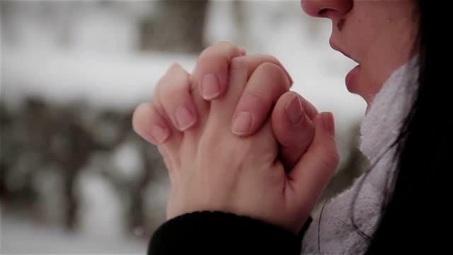 zamrażanie zimne kobiety w burzy śnieżnej biały obecnie próbuje utrzymać ciepło przez dmuchanie w jego ręce - zima filmów i materiałów b-roll