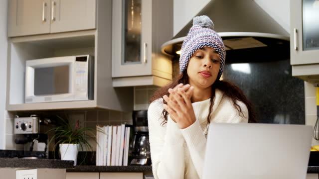 vidéos et rushes de congélation de femme en laine à l'aide de son ordinateur portable 4k 4k - froid
