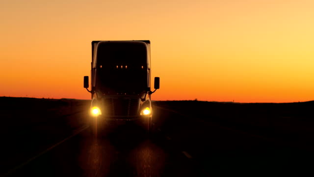 CLOSE UP: Freight container semi truck hauling along the country highway at dusk video