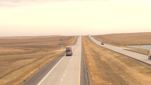 AERIAL: Freight container semi trucks hauling goods driving on rural highway video