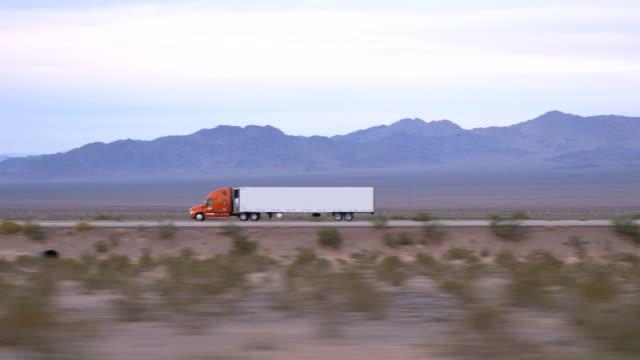 vídeos de stock, filmes e b-roll de perto de : carga semi caminhão dirigindo e o transporte de mercadorias na auto-estrada vazia - carregamento atividade