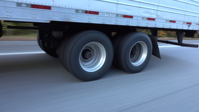 CLOSE UP: Freight semi truck passing by on highway, tires and wheels rolling