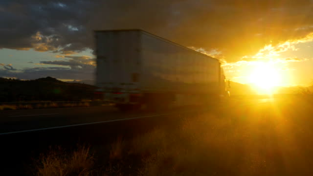Freight semi truck speeding on empty highway over golden sun at summer sunset CLOSE UP: Freight semi truck speeding on empty highway over golden sun at summer sunset. Transporting truck driving on freeway in sunny morning. semi truck stock videos & royalty-free footage