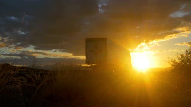 fracht sattelschlepper beschleunigung auf leere autobahn über die goldenen sonne im sommer sonnenuntergang - straßenfracht stock-videos und b-roll-filmmaterial