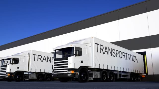 freight semi truck with transportation caption on the trailer loading or unloading. road cargo transportation. seamless loop fullhd clip - колонна стоковые видео и кадры b-roll