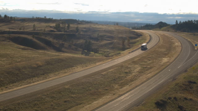 AERIAL: Freight trailer truck hauling goods along rural hilly landscape highway video