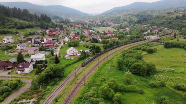 godståg bär ett elektriskt lokomotiv vid järnväg i skogen karpaterna berg. flygfotografering drone bred bild på sommaren. - karpaterna tåg bildbanksvideor och videomaterial från bakom kulisserna