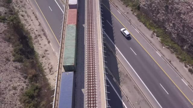 Freight Train crossing a highway bridge with traffic passing below.