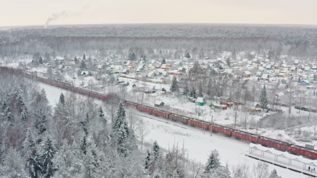 freight train moving through winter forest aerial drone view of freight train moving through winter snowy forest siberia stock videos & royalty-free footage