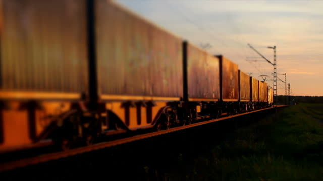 freight train passing by at sunset - train stock videos and b-roll footage
