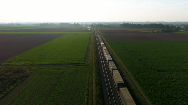 freight train passing through countryside in the afternoon - train stock videos and b-roll footage