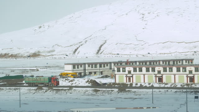 SLOW MOTION: Freight truck carries cargo past a small rural town in Tibet.
