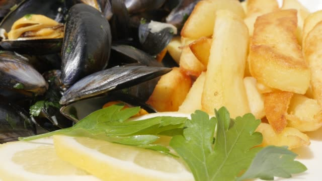 french chips  fries and blue common mussels with lemon close-up - belgio video stock e b–roll