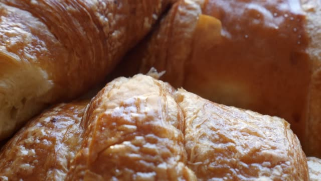 french famous croissant tasty dough rolls 4k 2160p 30fps ultrahd footage - viennoiserie buttery vienna-style pastry arranged on table 4k 3840x2160 uhd video - полумесяц форма предмета стоковые видео и кадры b-roll