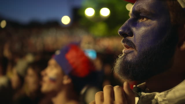 vídeos de stock e filmes b-roll de french fan with paint face worried against background crowd from loss his team - soccer supporter portrait