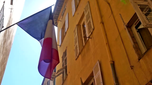 French flag hanging in a street French flag hanging in a small street in the city of Nice bastille day stock videos & royalty-free footage