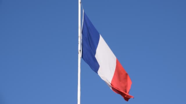 French flag with clear blue sky background French flag on post with blue sky background detail bastille day stock videos & royalty-free footage