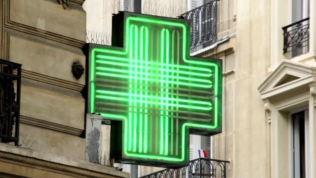 franska blinkande apotek skylt i paris med flaggan bakom - korsform bildbanksvideor och videomaterial från bakom kulisserna