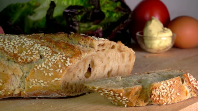 French freshly baked cereal baguette with sesame seeds cut with a knife
