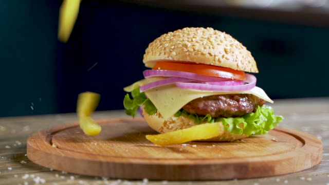 French fries falls on a served table with a hamburger in Slow motion. Eating burgers on dinner. Closeup. Сoncept of modern fast food: organic meat, farm ingredients, healthy foods.