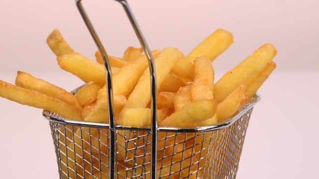 French fries in a small iron frying basket on turntable French fries in a small iron frying basket on turntable french fries stock videos & royalty-free footage
