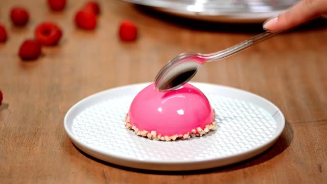 french mousse cake covered with raspberry glaze. pink modern european dessert. - десерт стоковые видео и кадры b-roll