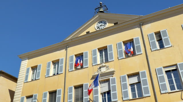 French town hall building, Hotel de Ville (Mairie), in Antibes The facade of the town hall (Mairie / Hotel de Ville) in Antibes, yellow with blue shutters, clock and bell and french flags flying, against a clear blue sky. french architecture stock videos & royalty-free footage