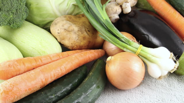 fresh and organic cabbage, zucchini, eggplant, onion, carrot, potato, broccoli and mushrooms on the table. close up pile of vegetables - aglio cipolla isolated video stock e b–roll