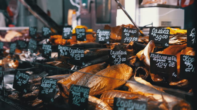 fresh and smoked fish with price tags are on sale in the shop window - banchi di pesci video stock e b–roll