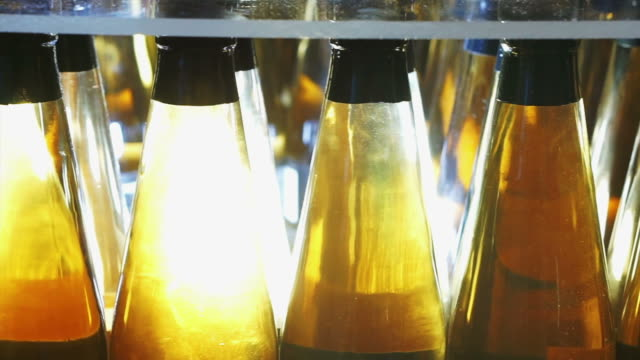 vídeos de stock e filmes b-roll de fresh apple cider in bottle package with lighting showing clear gold transparent alcohol - vinagre