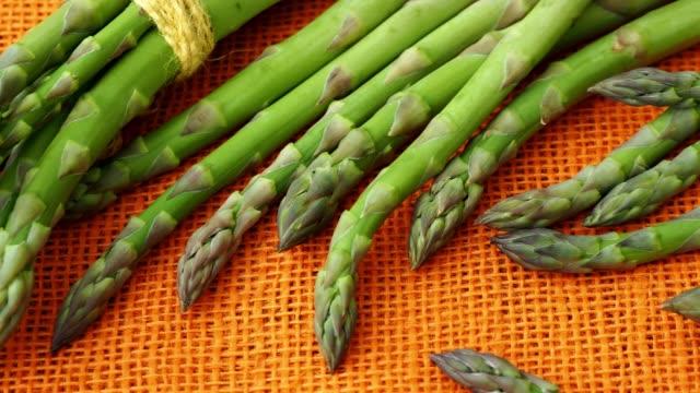Fresh asparagus officinalis on orange background. Raw garden asparagus stems. video