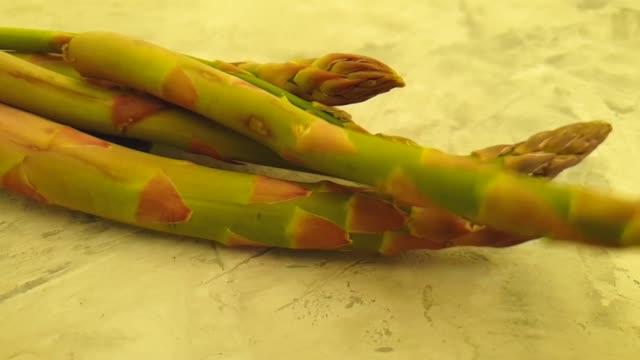 fresh asparagus on gray concrete background, slow motion