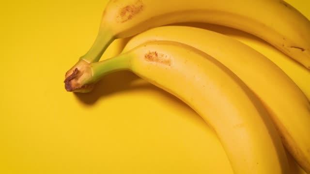 vidéos et rushes de bananes fraîches sur fond minimaliste jaune - en botte ou en grappe