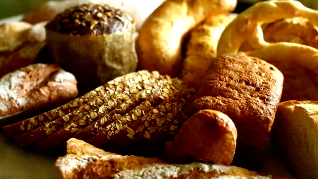 Fresh breads and rolls. Arrangement of freshly baked breads and rolls. Made of processed and wholegrain flower. Horizontal pan, side view. pastry dough stock videos & royalty-free footage