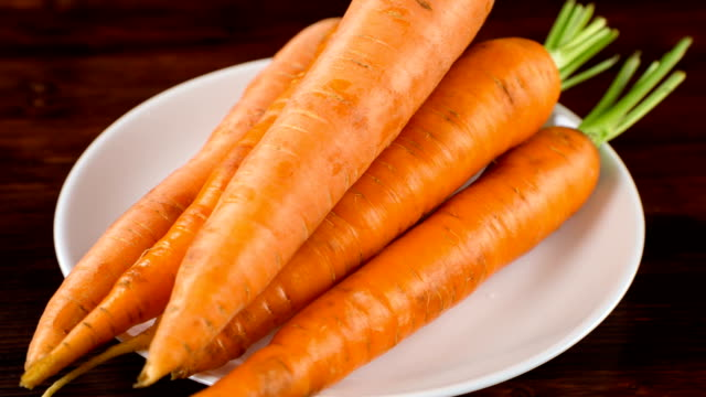 fresh carrots lying on white plate fresh carrots lying on white plate on wooden table, dolly shot carrot stock videos & royalty-free footage
