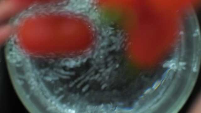 Fresh cherry tomato splashing into the water slow motion video video