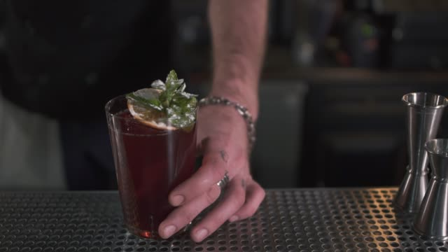 Fresh cocktail decorated with mint and orange standing on bar counter video